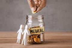 medyczny Szklany słój z monetami i inskrypcją jest medyczny i symbolu rodzina lub para Mężczyzna chwytów moneta w ręce zdjęcie stock