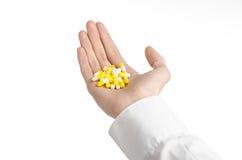 Medyczny temat: lekarki ręka trzyma żółtą kapsułę odizolowywająca dla zdrowie na białym tle Obraz Stock