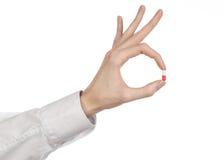 Medyczny temat: lekarki ręka trzyma czerwoną kapsułę odizolowywająca dla zdrowie na białym tle Fotografia Stock