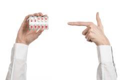 Medyczny temat: lekarki ręka trzyma czerwoną kapsułę odizolowywająca dla zdrowie na białym tle Zdjęcia Royalty Free