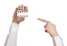 Medyczny temat: lekarki ręka trzyma czerwoną kapsułę odizolowywająca dla zdrowie na białym tle Obraz Royalty Free