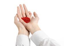 Medyczny temat: lekarki ręka trzyma czerwoną kapsułę odizolowywająca dla zdrowie na białym tle Zdjęcia Stock