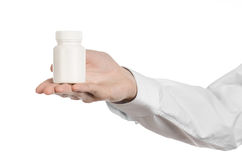 Medyczny temat: lekarki ręka trzyma białego opróżnia słój pigułki na białym tle Zdjęcie Royalty Free
