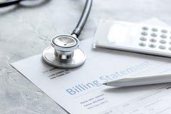 Medyczny treatmant fakturowania oświadczenie z stetoskopem i kalkulatorem na kamiennym tle zdjęcie stock