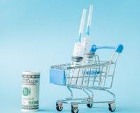Medyczny zastrzyk i dolary w zakupy tramwaju na b??kitnym tle Kreatywnie pomys? dla koszt opieki zdrowotnej, apteka, zdrowie fotografia stock