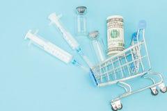 Medyczny zastrzyk i dolary w zakupy tramwaju na b??kitnym tle Kreatywnie pomys? dla koszt opieki zdrowotnej, apteka, zdrowie zdjęcia stock