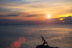Medytaci dziewczyna na morzu podczas zmierzchu Joga sylwetka Zdjęcia Stock