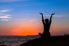 Medytaci joga kobiety sylwetka na morzu podczas zadziwiającego zmierzchu Obrazy Stock