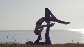 Medytacja na na wolnym powietrzu, kobiecie i mężczyźnie robi pary joga na górze na tle, morze i zmierzch zdjęcie wideo