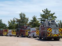 Meeeting In The Park`s Pool Area. Unusual to see a fire truck, Rescue Squad, fire truck, Rescue Squad, fire truck liked up in a park. The trucks and Squads are royalty free stock images