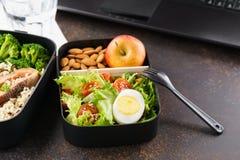 Meeneemlunchdozen met voedsel bij werkend bureau met laptop royalty-vrije stock afbeelding