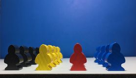 Meeples in front of blue wall perfect for boardgames. royalty free stock photos