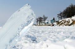 Meer Baikal in de winter Grote Eenzame ijsschol op achtergrond van kust met blokhuis en bos royalty-vrije stock afbeeldingen