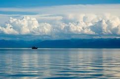 Meer Baikal, het schip tegen bergen en wolken Stock Foto