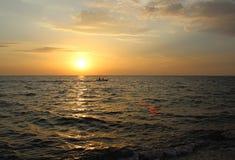 Meer bei Sonnenuntergang, Leute schwimmen durch Boot Lizenzfreie Stockfotos