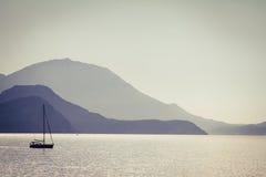Meer, Berge und ein Fischerboot Stockbilder