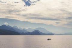 Meer, Berge und ein Fischerboot Stockfotografie