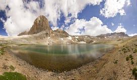 Meer in bergen met grote rots in Turkije Aladaglar Stock Afbeeldingen