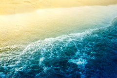 Meer bewegt mit goldenem Sand wellenartig Stockfotos