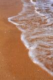 Meer bewegt Schaumgummi auf dem Strand wellenartig Stockfotografie