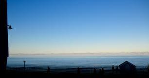Meer in der Dämmerung, Leute, die entlang den Strand gehen Lizenzfreies Stockfoto