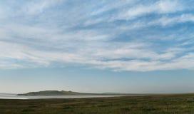Meer en heuvels onder een blauwe hemel met wolken Royalty-vrije Stock Foto's