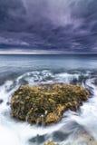 Meer, Felsen und Schaumgummi unter einem stürmischen Himmel. Lizenzfreie Stockfotos
