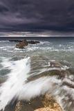 Meer, Felsen und Schaumgummi unter einem stürmischen Himmel. Lizenzfreie Stockbilder