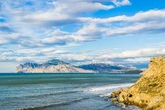 Meer, Himmel, Wolken, Berge, sandiger Strand Lizenzfreies Stockfoto
