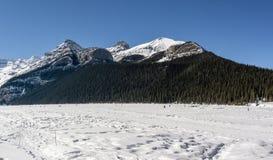 Meer Louise, CANADA - MAART 20, 2019: bevroren meer en bergen met sneeuwpieken stock afbeelding