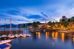 Meer Maggiore, Laveno, Noord-Italië Mening bij zonsopgang van de mooie kleine en oude haven en van de oever van het meerpromenade Royalty-vrije Stock Afbeeldingen