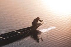 Meer met bezinning van de zon en een persoon die van een boot vissen stock afbeelding