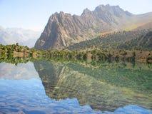 Meer met weerspiegeling van bergpieken stock afbeelding