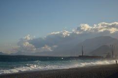 Meer mit anhebendem Kran und Wolken Stockfotos