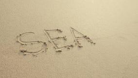 MEER mit dem Herzen, das auf den Strandsand geschrieben wurde, wusch sich immer durch Wellen Stockfotos