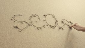 MEER mit dem Herzen, das auf den Strandsand geschrieben wurde, wusch sich immer durch Wellen Lizenzfreie Stockbilder