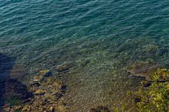Meer mit einer Steinunterseite und blauen klaren Wasser Stockfoto