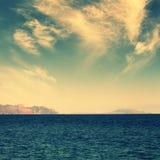 Meer mit Insel auf Horizont, Weinlesefarben Stockfoto
