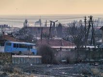 Meer, Morgen, die Industrie und der blaue Bus Stockbild