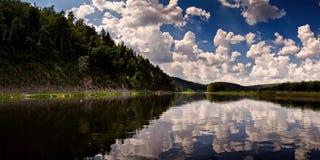 Meer onder heuvels met bezinningen van wolken in de hemel Stock Afbeelding