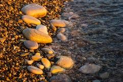 Meer Pebble Beach mit mehrfarbigen Steinen, Wellen mit Schaum Lizenzfreies Stockbild