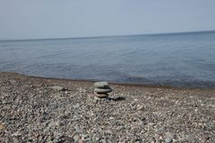 Meer Pebble Beach mit Steinen, transparente Wellen mit Schaum, an einem warmen Sommertag Schindelstrand stockbild
