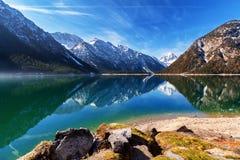 Meer Plansee met bergen die in het water, Tirol, Oostenrijk nadenken stock afbeeldingen