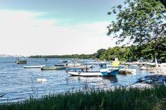 Meer sonniger Tag Fischer Fischerboote der Boote und Gebirgsblaues Seemeer und -bäume lizenzfreie stockfotografie