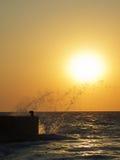 Meer spritzt am Sonnenuntergang Stockbilder