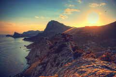 Meer und Berge bei Sonnenuntergang Blauer Himmel und blanke Hügel Feld des grünen Grases gegen einen blauen Himmel mit wispy weiß Lizenzfreies Stockbild