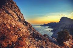 Meer und Berge bei Sonnenuntergang Blauer Himmel und blanke Hügel Feld des grünen Grases gegen einen blauen Himmel mit wispy weiß Stockfotografie