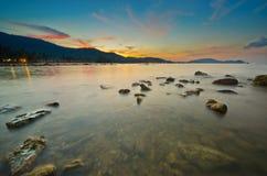 Meer und Felsen auf dem Strand mit Sonnenuntergang lizenzfreies stockbild