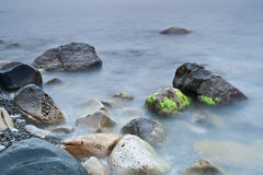 Meer und Felsen am Sonnenuntergang. Stockfotos