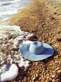 Meer- und Frauen `s Hut auf einem Schindel setzen auf den Strand Stockfoto